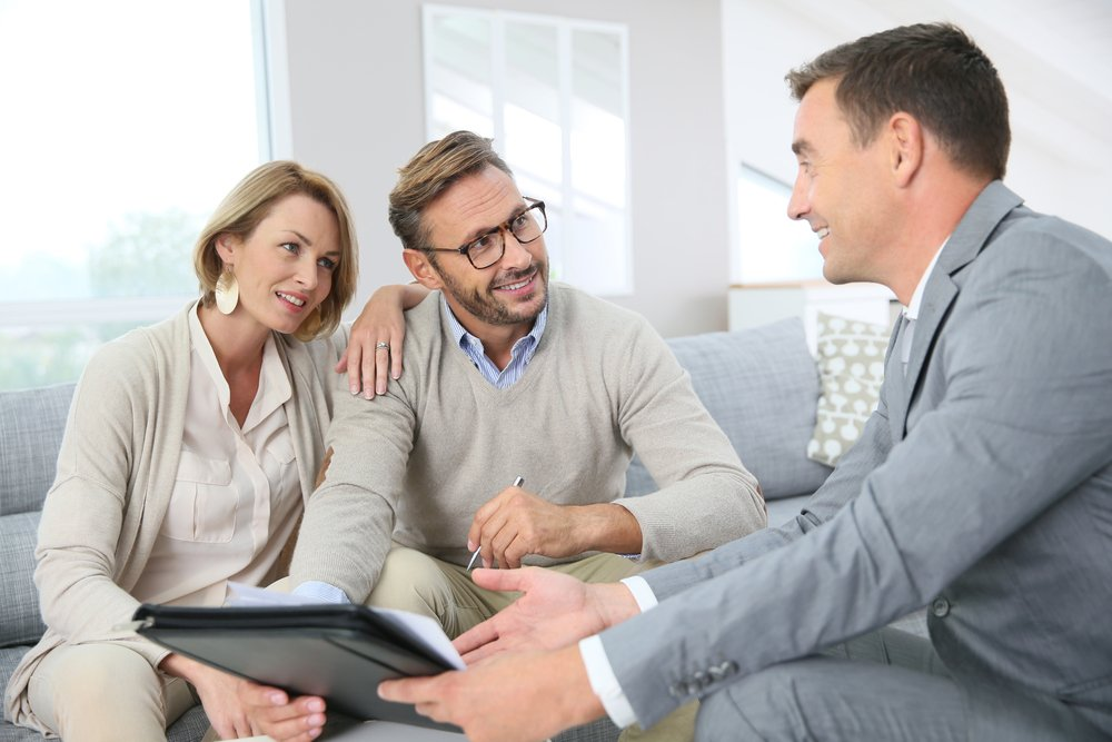 Couple with realtor signing mortgage contract-1